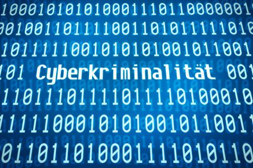 """Weißer Binärcode auf blauem Hintergrund mit dem eingeflochtenem Wort """"Cyberkriminalität"""""""